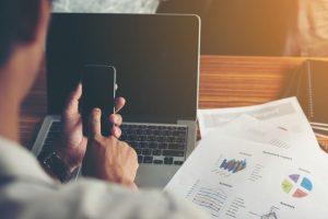 ręce-biznesmen-przy-użyciu-telefonu-komorkowego-z-raportu-finansowego-na-off_1150-644